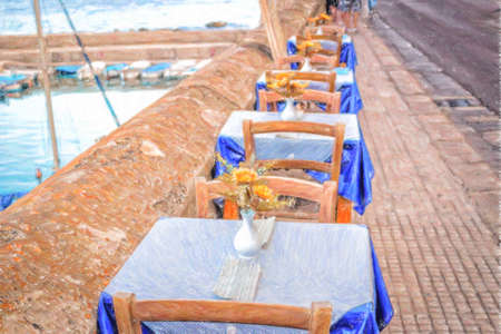 Dinner tables in Italian restaurant on brown stone parapet on the sea bay of Gallipoli (Le) in Italy in a summer sunny day: plastic fake yellow flowers with large petals and green leaves in white vase, White and blue gingham napkins and tablecloth  on ele