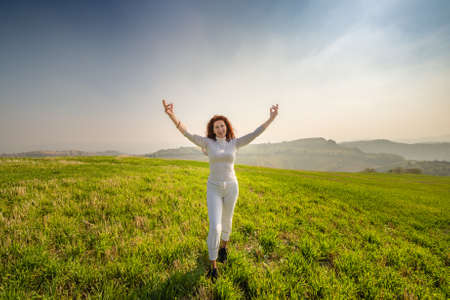 Menopausal woman raising arms on hilly countryside in sunny day