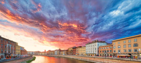 Colorful red and blue scenic sunset sky with clouds on river in Pisa, Italy