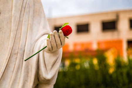 statue of Our Lady of Medjugorje, the Blessed Virgin Mary, with red rose in hand Stock Photo