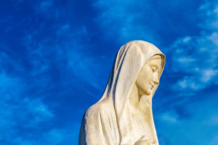 statue of Our Lady of Medjugorje, the Blessed Virgin Mary, against blue sky