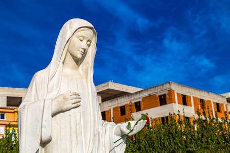 standbeeld van Onze-Lieve-Vrouw van Medjugorje, de Heilige Maagd Maria, tegen blauwe hemel en in aanbouw huizen