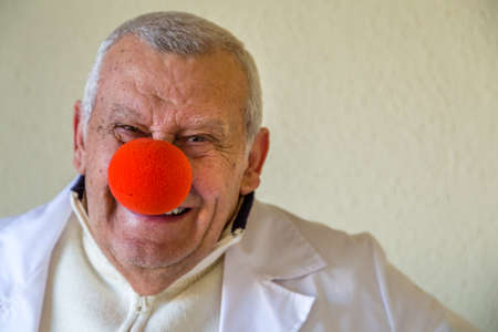 old country doctor with clown red nose smiling