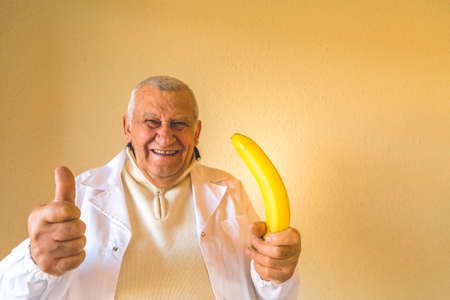 Old country doctor smiling while showing thumbs up and holding a large erect banana as concept of treating impotence Stock Photo