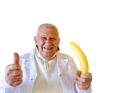 Old country doctor smiling while showing thumbs up and holding a large  banana