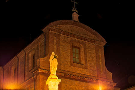 night view of statue of the Blessed Virgin Mary holding white roses in front of ancient church