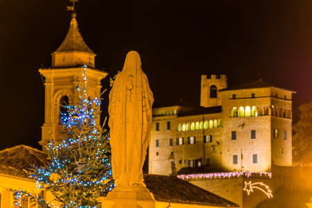 night view of back of statue of the Blessed Virgin Mary in front of ancient castle at christmas