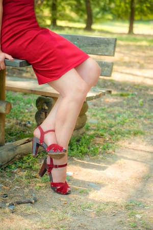 beautiful and sinuous crossed legs of classy woman, bandaged by a red dress with high-heeled sandals Banco de Imagens