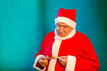 sad old man wearing Santa Claus costume measuring the circumference of his belly with a tape measure