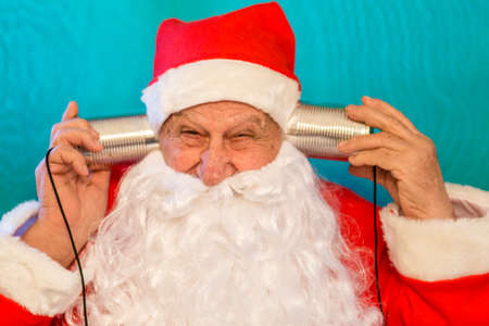 old man wearing Santa Claus costume talking with two tin can telephone