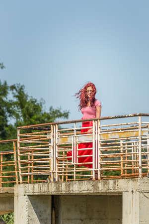 自由感を生きる古い錆びた鉄橋の上を歩く赤い桜の毛の少女