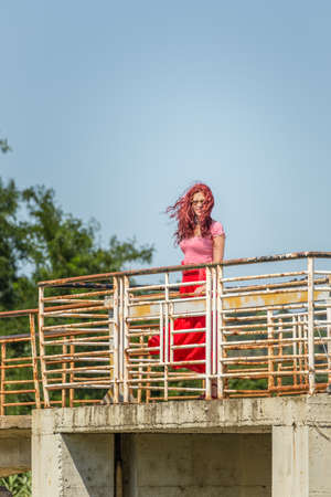 red cherry haired girl walking on an old rusty iron bridge living the sense of freedom