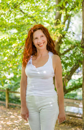 happy woman in menopause standing and smiling in a garden, joyfully living the change of life 스톡 콘텐츠