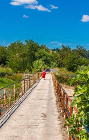 古い錆びた鉄橋の上を歩き、自由の感覚を生きる腕を上げる少女 写真素材