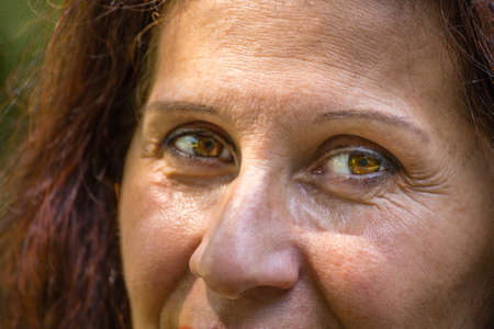 cerca de ojos de mujer madura con cabello castaño rojizo, arrugas y patas de gallo y con leve estrabismo de Venus Foto de archivo