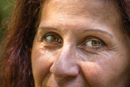 Nahaufnahme der Augen der reifen Frau mit rotbraunen Haaren, Falten und Krähenfüßen und mit leichtem Strabismus der Venus Standard-Bild