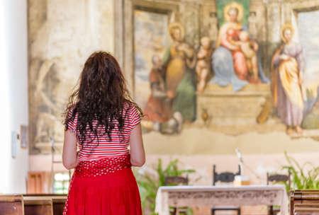 achterkant van de Latijnse vrouw, die in de katholieke kerk bidt en de spiritualiteit van de plaats leeft