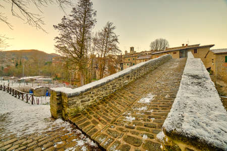 Ancient medieval donkey-back bridge with a unique arch in a village in the hills of Romagna in Italy under white snow