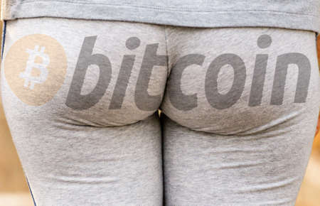 Public domain bitcoin logo on sexy buttocks in gray gym suit, young woman is walking