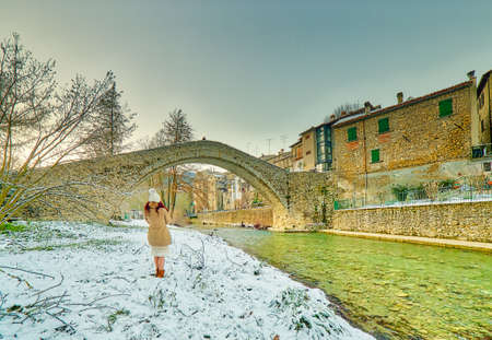 woman near Ancient medieval donkey-back bridge with a unique arch in a village in the hills of Romagna in Italy under white snow Stock Photo