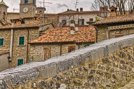 view of roofs of cozy Italian medieval village from ancient bridge