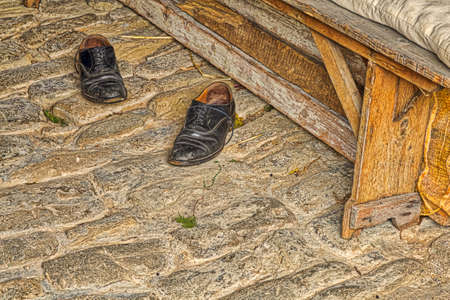 Beat Black leather shoes left by old farmer on ancient stone road near grunge wooden bench