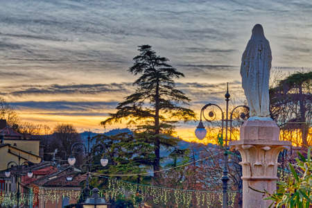 winter sunset on the statue ot the Blessed Virgin Mary looking at Italian medieval village Stock Photo