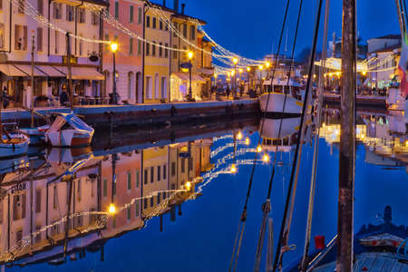 blue hour at sunset on the Christmas decorations of port channel of Cesenatico, best tourist destination of the Romagna Riviera in Italy