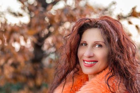 Closeup of a smiling mature woman with slight strabismus of Venus wearing orange fur collar and showing wrinkles, feet of crow and other aging defects on autumnal nature background