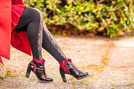 Nahaufnahme von gewundenen und sinnlichen Beinen mit Stiefeln mit hohen Absätzen und sexy Strumpfhosen