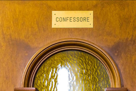 wood confessional door with Italian word meaning confessor