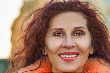 Closeup of a beautiful smiling mature woman with wrinkles and slight strabismus of Venus wearing orange fur collar