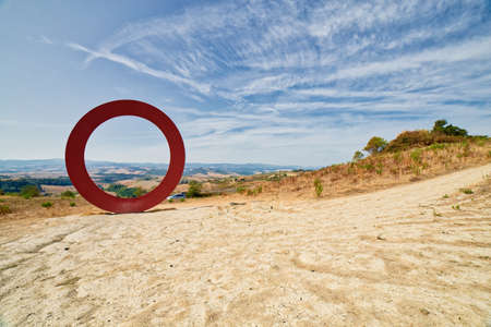 sculpture of Mauro Staccioli framing Tuscan countryside is unusual but popular tourist attraction Stock Photo