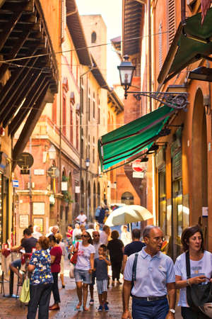 BOLOGNA, ITALY - AUGUST 27, 2016:  tourists and locals go shopping in medieval market. The trade vocation of this area known as Quadrilatero, meaning The Quadrilateral Area, was born in Middle Ages Editorial