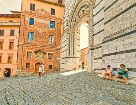 SIENA, ITALY - AUGUST 28, 2017: tourists walk and seek shelter from the summer heat in the street of Siena in Italy Editorial