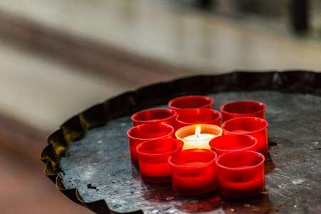 one white candle burning amongst extinguished red ones
