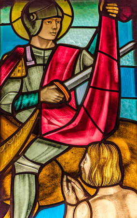 LUGO (RA) - FEBRUARY, 21 2018: the young soldier Saint Martin of Tours cut his cloak  in half with sword to give it to a beggar, in a stained glass in country church Editorial