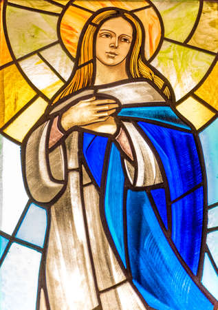 LUGO (RA) - FEBRUARY, 21 2018: The Blessed Virgin Mary holding hands on chest in a stained glass in country church