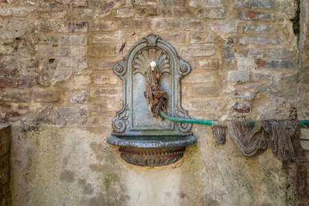 rusty iron fountain on old scraped wall