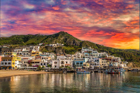 sunset on higgledy-piggledy piled houses on bay of Ischia island, Naples in Italy Фото со стока