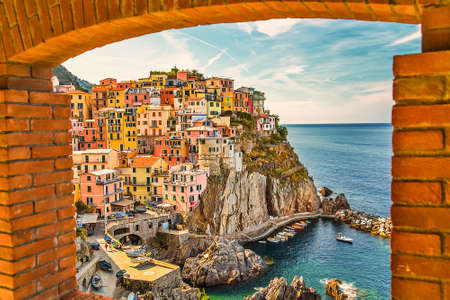 view of colorful fishing houses in Italian sea town from ancient brick window