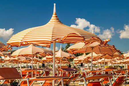 wind on orange stripes sunshades in Italian seaside Stock Photo