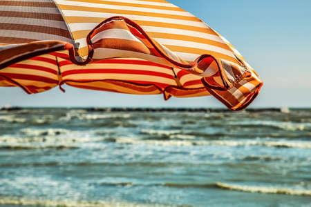 wind on orange stripes sunshade in Italian seaside Stock Photo