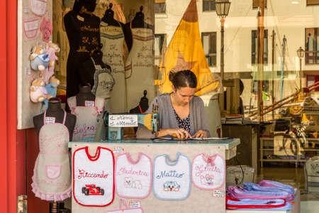 CESENATICO (FC), ITALY - JUNE 23, 2018: Embroiderer makes embroidery for tourists Foto de archivo - 103975066