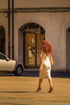 red girl in pencil dress and high heels  walking in urban parking area