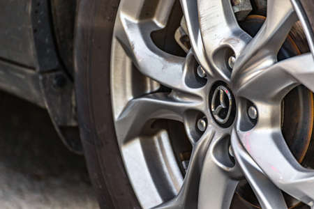 RAVENNA, ITALY - JUNE 30, 2018: Dirt and dust cover the MAZDA logo on an alloy wheel