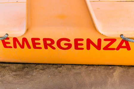 yellow lifeboat with Italian word meaning Emergency on sandy beach