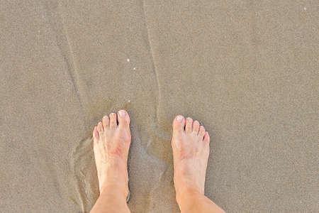 female wet feet on seaside