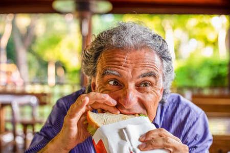 Funny tourist eating organic sandwich in Italian countryside