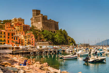 LERICI (SP), ITALY - JUNE 21, 2018: tourists are sunbathing while waters are wetting the hulls of the boats in the marina of Lerici